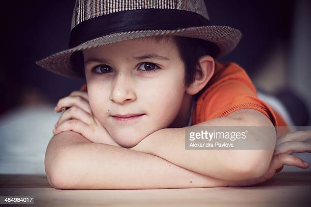 cute boy with hat, relaxed, propping chin on hands - alexandra pavlova stock pictures, royalty-free photos & images