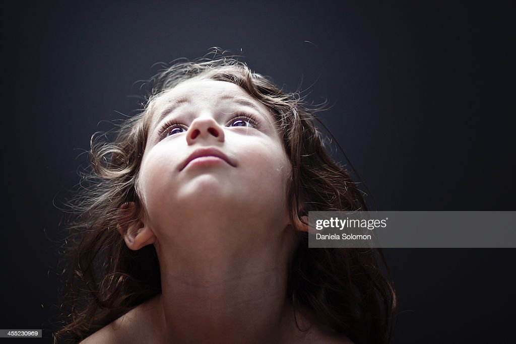 Cute boy with long hair looking up and praying : Stock Photo