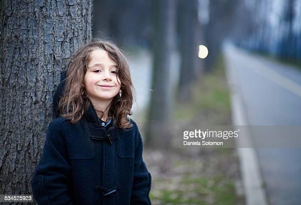 Cute boy with long hair near a tree