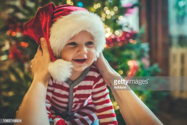 cute boy with mother near christmas tree indoors - hat stock pictures, royalty-free photos & images