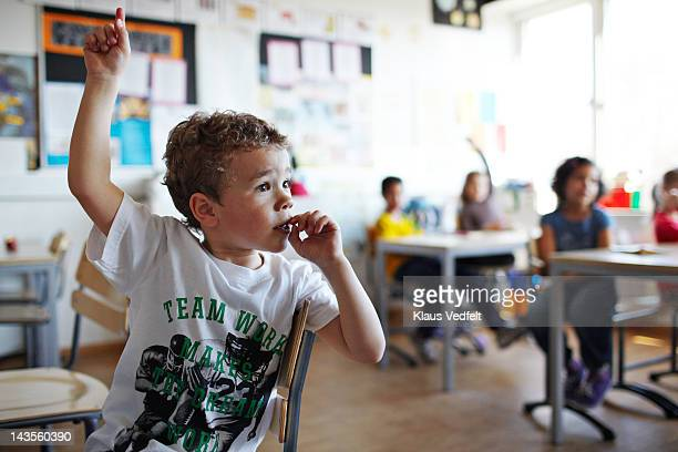 cute boy with raised hand in classroom - danemark photos et images de collection
