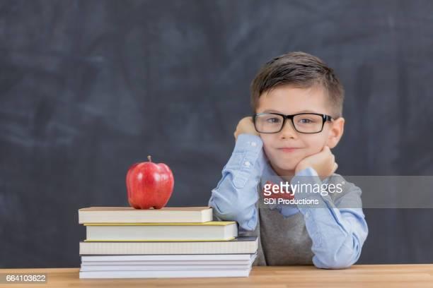 Süsser Boy mit Stapel Bücher im Klassenzimmer