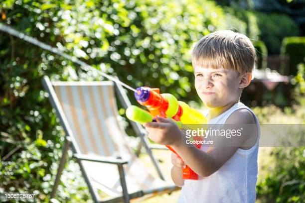 cute boy with water gun. - shooting at goal stock pictures, royalty-free photos & images