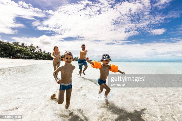 cute boys running away from their parents on the beach. - family beach holiday stock pictures, royalty-free photos & images