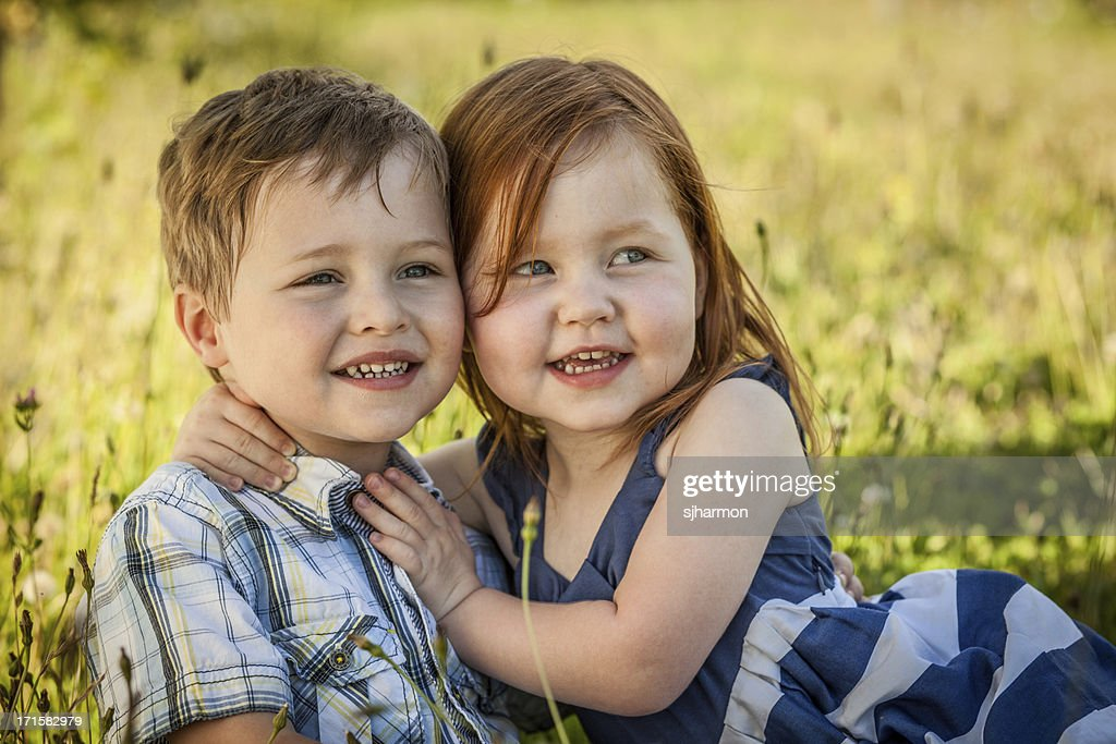 Cute Brother And Sister Hugging In Field On Summer Day Stock Photo