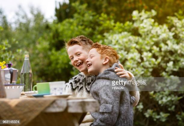 niedliche brüder lachen am tisch im hinterhof - bruder stock-fotos und bilder