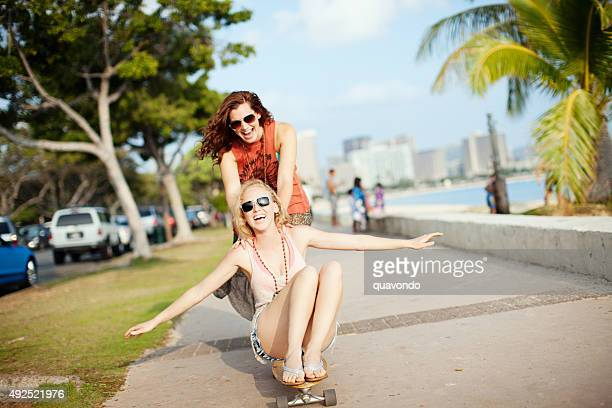 Cute Brunette and Blonde Playing On Skateboard On Sunny Day
