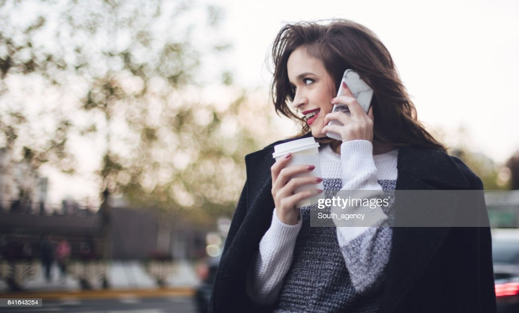 cute brunette girl talking on the phone stock photo | getty images