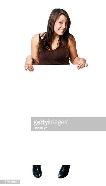Cute brunette stands behind blank sign ready for your message