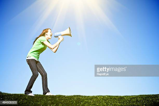 Cute brunette yells enthusiastically into bullhorn, coaching, encouraging, or protesting