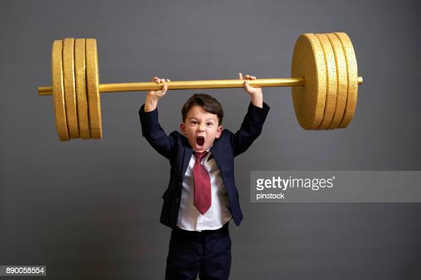 cute business boy lifting gold barbell - weight training stock pictures, royalty-free photos & images