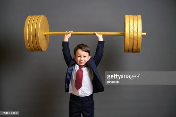 cute business boy lifting gold barbell - improvement stock pictures, royalty-free photos & images