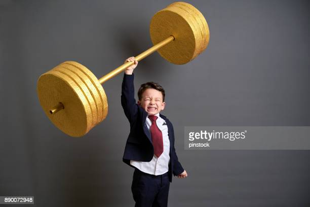 cute business boy lifting gold barbell - turnover sport stock photos and pictures