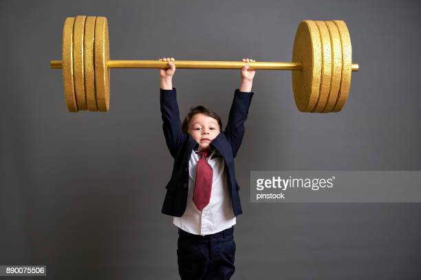 Cute business boy lifting gold barbell