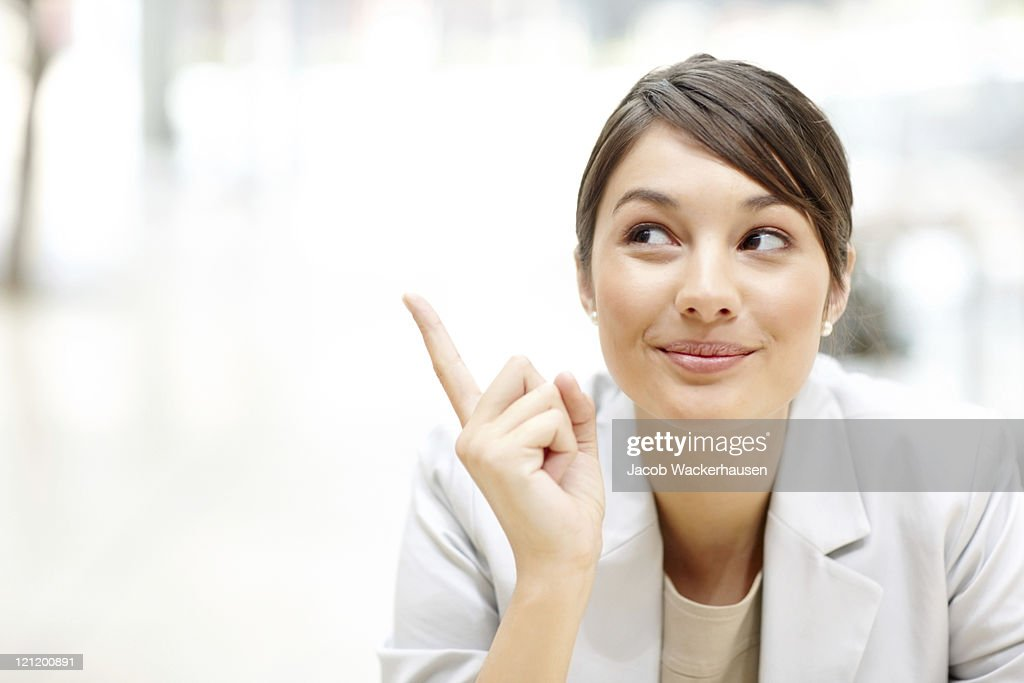 Cute businesswoman looking and pointing at copyspace : Stock Photo