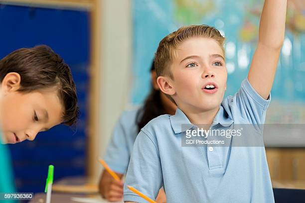 Cute Caucasian boy raises hand to answer question in class