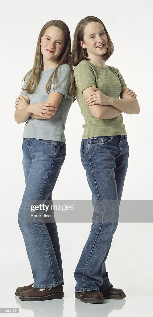 cute caucasian teenage sisters stand back to back with arms folded : Foto de stock