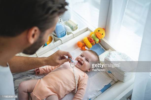 cute cheerful baby and her father in a nursery - baby changing mat stock pictures, royalty-free photos & images