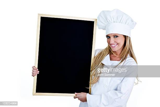 Cute chef holding a blackboard for copy space