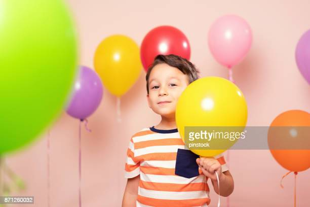 Cute child among colorful balloons.