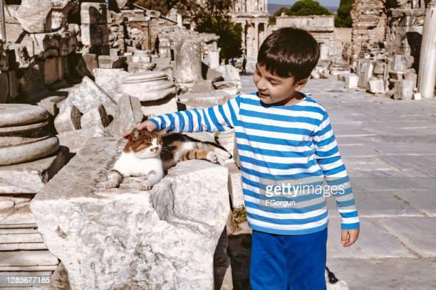 lindo niño y gato cura la calle en efeso - arqueología fotografías e imágenes de stock