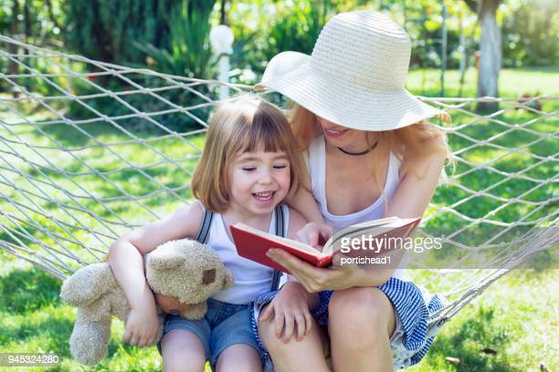 Cute child and his mommy having fun on hammock