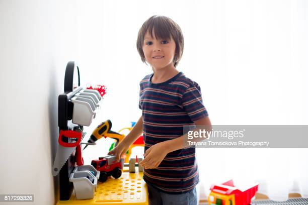 Cute child boy playing  indoors at home in his playroom with colorful plastic toys
