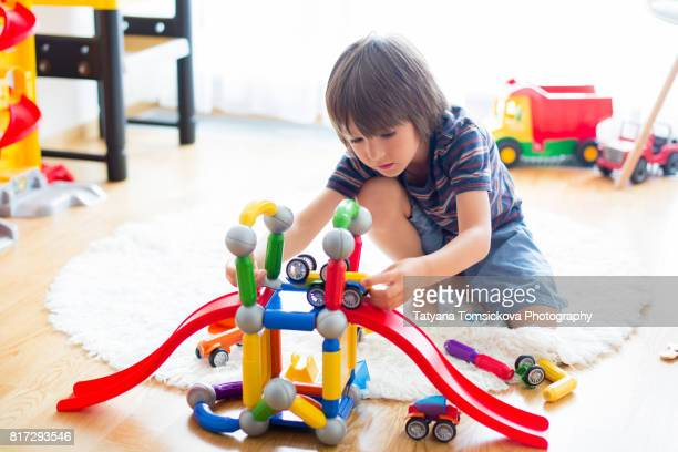 Cute child boy playing  indoors at home in his playroom with colorful plastic magnetic toys