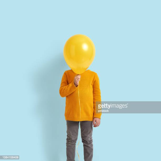 bonita criança segurando um balão amarelo - amarelo - fotografias e filmes do acervo
