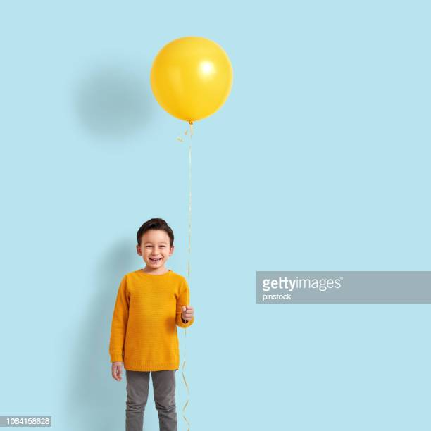 cute child holding a yellow balloon - celebration stock pictures, royalty-free photos & images