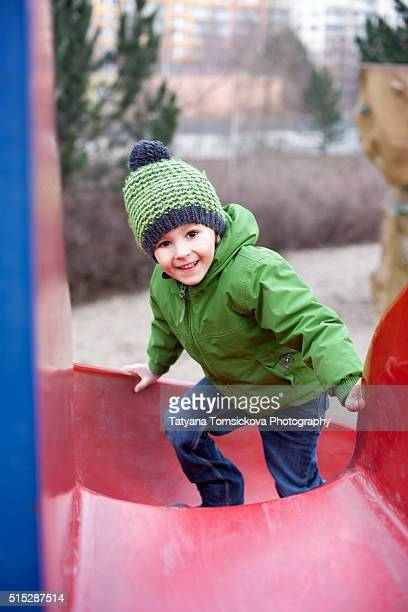 Cute child, preschooler boy, excitedly plays on playground slide on a cool cloudy day