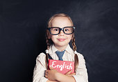 Cute child schoolgirl holding red book on chalkboard background. Speak english and learn language concept