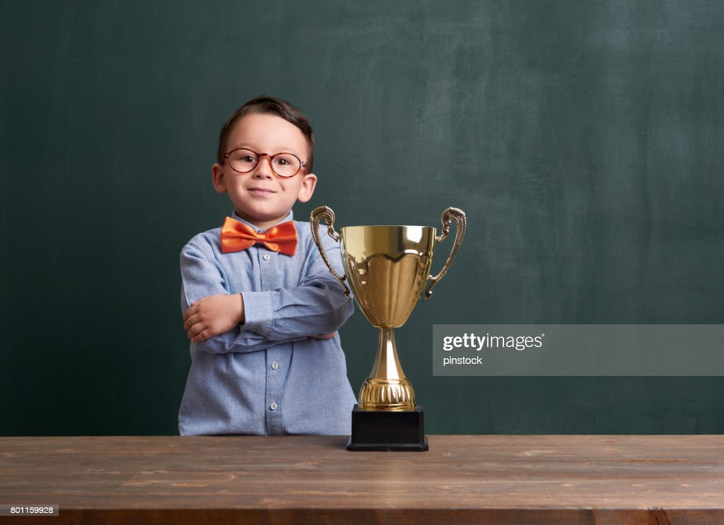 Cute child with a golden trophy : Stock Photo