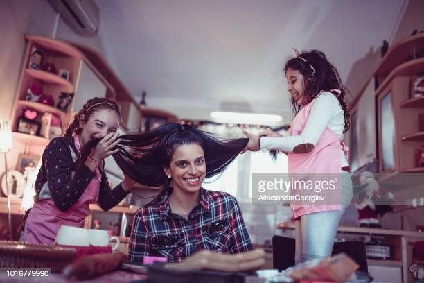Cute Children Having Fun With Mother's Hair In Kitchen