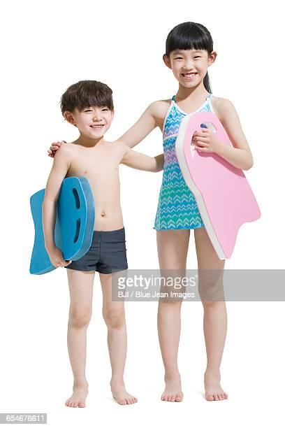 Cute children in swimsuit with kickboards