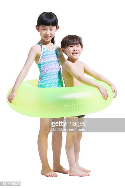 cute children in swimsuit with swim ring - ランニングショートパンツ ストックフォトと画像