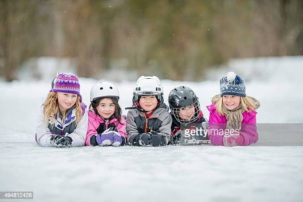 Cute Children Lying on a Frozen Lake