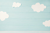 Cute children or baby card, white clouds on the light blue wooden background, tonned