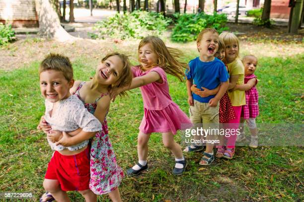 cute children playing at park - peuter stockfoto's en -beelden