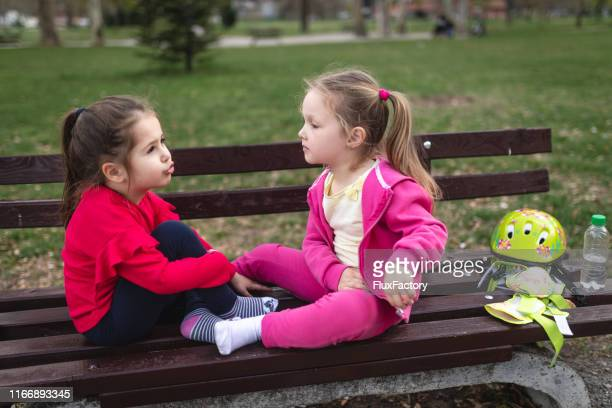 cute children sitting on a bench and talking - family with two children stock pictures, royalty-free photos & images