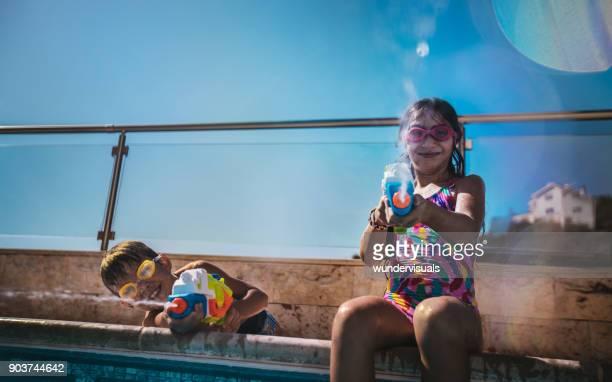 schattige kinderen spatten met water pistolen bij zwembad - cyprus stockfoto's en -beelden