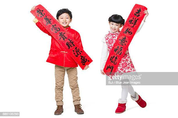 Cute children with couplets celebrating Chinese new year