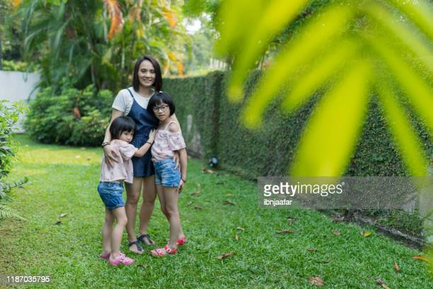 cute chinese asian siblings playing at garden house - ibnjaafar stock photos and pictures