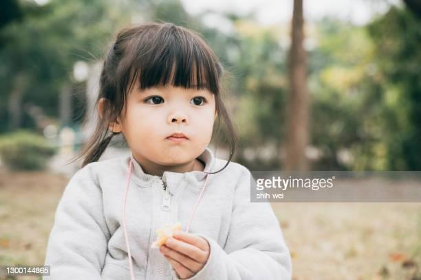 公園で朝食とピクニックをしているかわいい中国の女の子 - ヒトの口 ストックフォトと画像