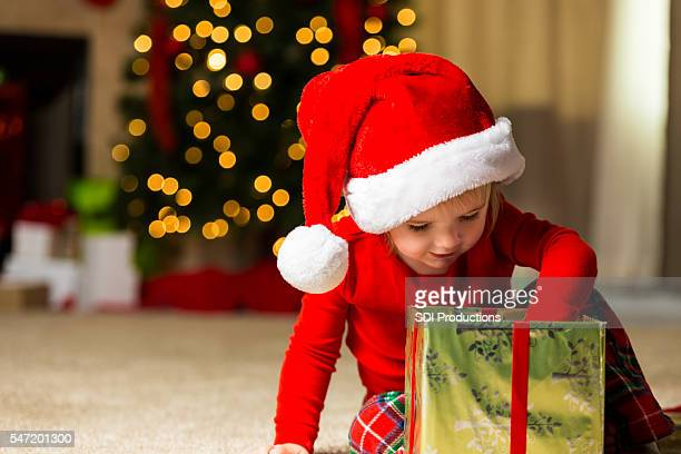 Cute Christmas toddler opening up a gift
