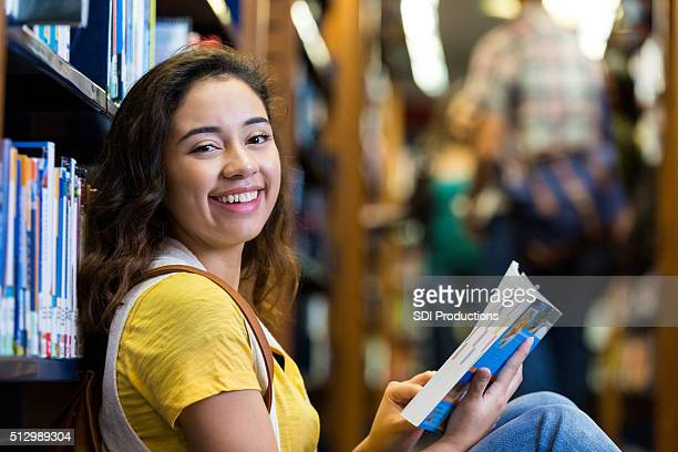 Cute college age girl reading a book while in library