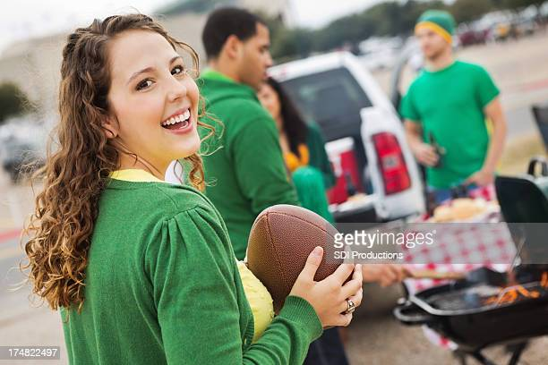 Cute college girl tailgating at stadium with football fans