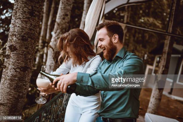 cute couple celebrating anniversary pouring champagne in glasses - drunk wife at party stock pictures, royalty-free photos & images