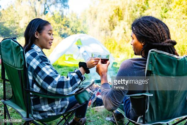 A cute couple enjoying a glass of wine beside the campfire.