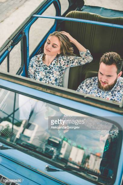 Cute Couple Enjoying The Wind While Driving a Convertible Vintage Car